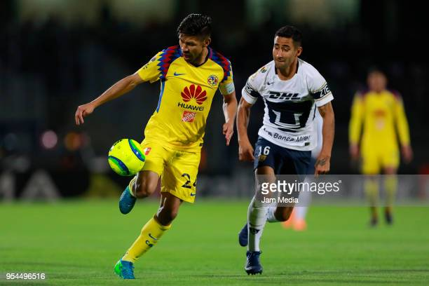 Oribe Peralta of America and Luis Fuentes of Pumas compete for the ball during the quarter finals first leg match between Pumas UNAM and America as...