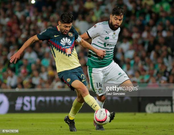 Oribe Peralta of America and Nestor Araujo of Santos fight for the ball during the 17th round match between Santos Laguna and America as part of the...