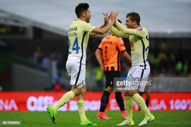 Oribe Peralta of America celebrates with teammates after scoring the first goal of his team during the 10th round match between America and Necaxa as...