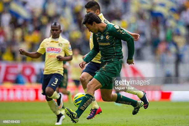 Oribe Peralta of America fights for the ball with Oswaldo Alanis of Santos during a match between America and Santos Laguna as part of 10th round...