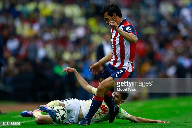 Oribe Peralta of America fights for the ball with Oswaldo Alanis of Chivas during the semifinal match between America and Chivas as part of the Copa...