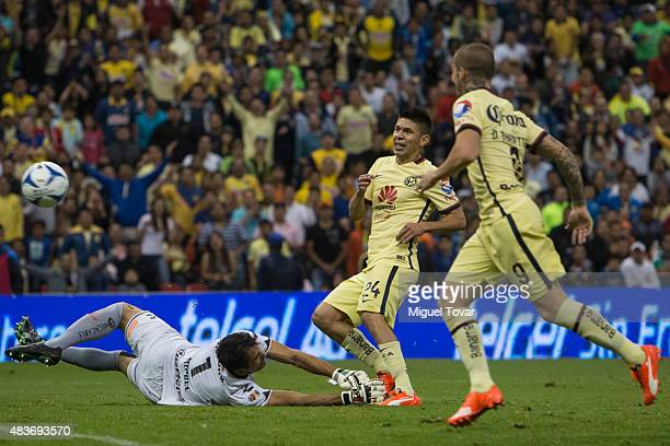 Oribe Peralta of America scores against Luis Michel of Dorados during a 4th round match between America and Dorados as part of the Apertura 2015 Liga...