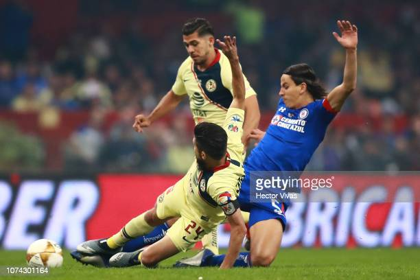Oribe Peralta of America struggles for the ball with Igor Lichnovsky of Cruz Azul during the final second leg match between Cruz Azul and America as...
