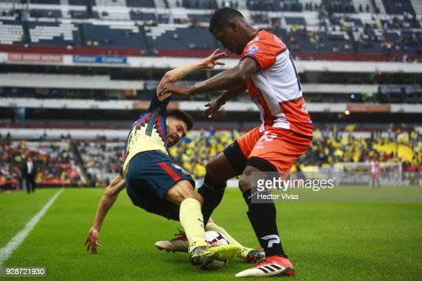 Oribe Peralta of America struggles for the ball with Richard Dixon of Tauro FC during the match between America and Tauro FC as part of the CONCACAF...