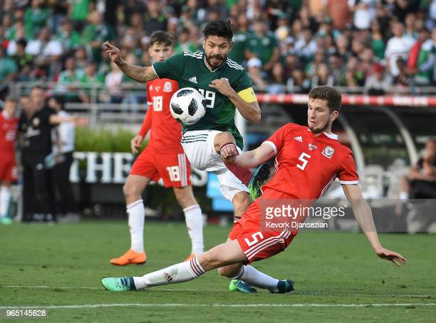 Oribe Peralta of Mexico attempts to shoot the ball again the defense of Chris Mepham of Wales during the second half of their friendly international...