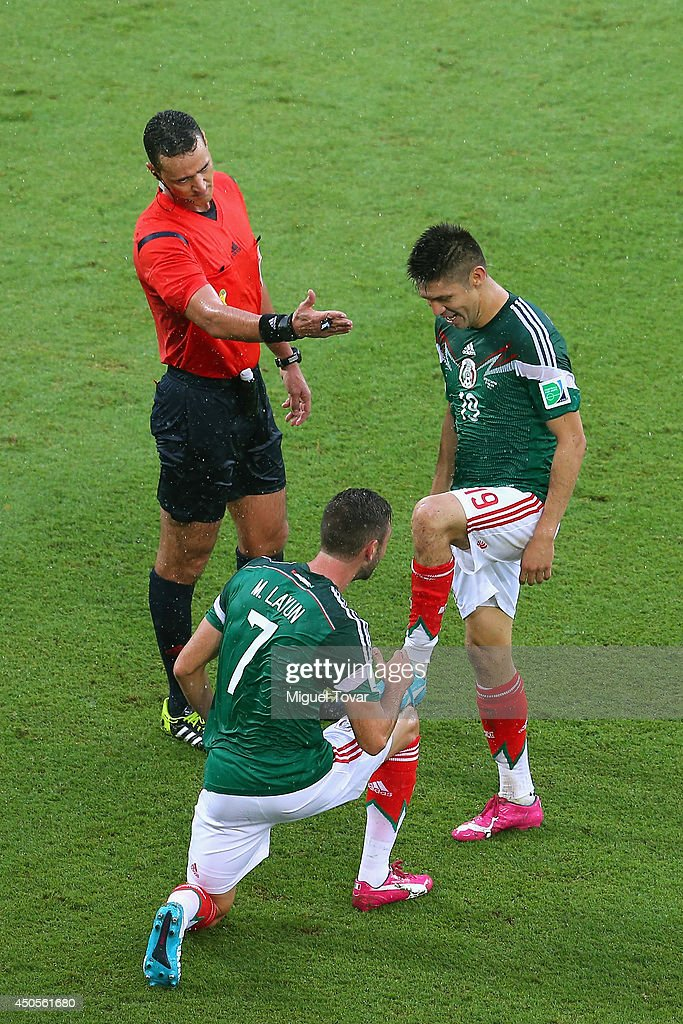 Oribe Peralta of Mexico (R) celebrates his goal with teammate Miguel Layun as referee Wilmar Roldan gestures during the 2014 FIFA World Cup Brazil Group A match between Mexico and Cameroon at Estadio das Dunas on June 13, 2014 in Natal, Brazil.