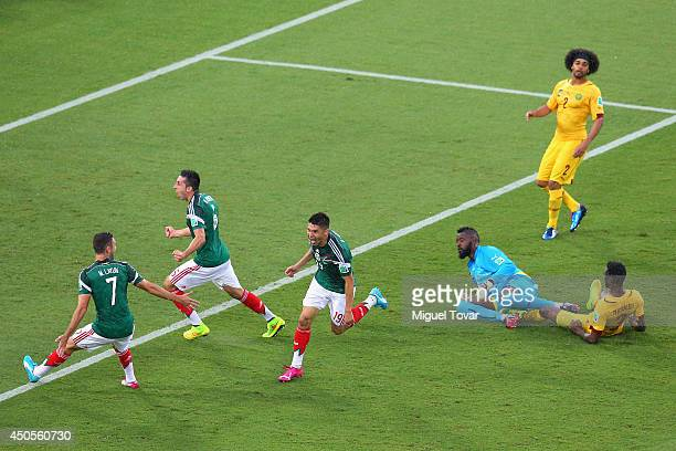 Oribe Peralta of Mexico celebrates his goal with teammates Miguel Layun and Hector Herrera as goalkeeper Charles Itandje of Cameroon looks on in the...