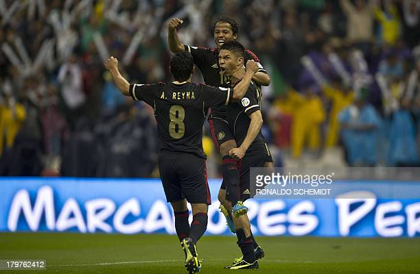 Oribe Peralta of Mexico celebrates with teammates Giovanni dos Santos and Angel Reyna after scoring against Honduras during their FIFA World Cup...