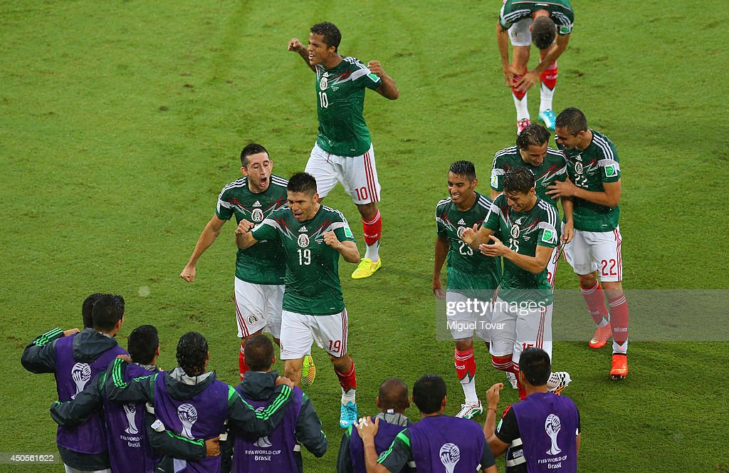 Oribe Peralta of Mexico (19) runs to the sidelines to celebrate his goal with teammates during the 2014 FIFA World Cup Brazil Group A match between Mexico and Cameroon at Estadio das Dunas on June 13, 2014 in Natal, Brazil.