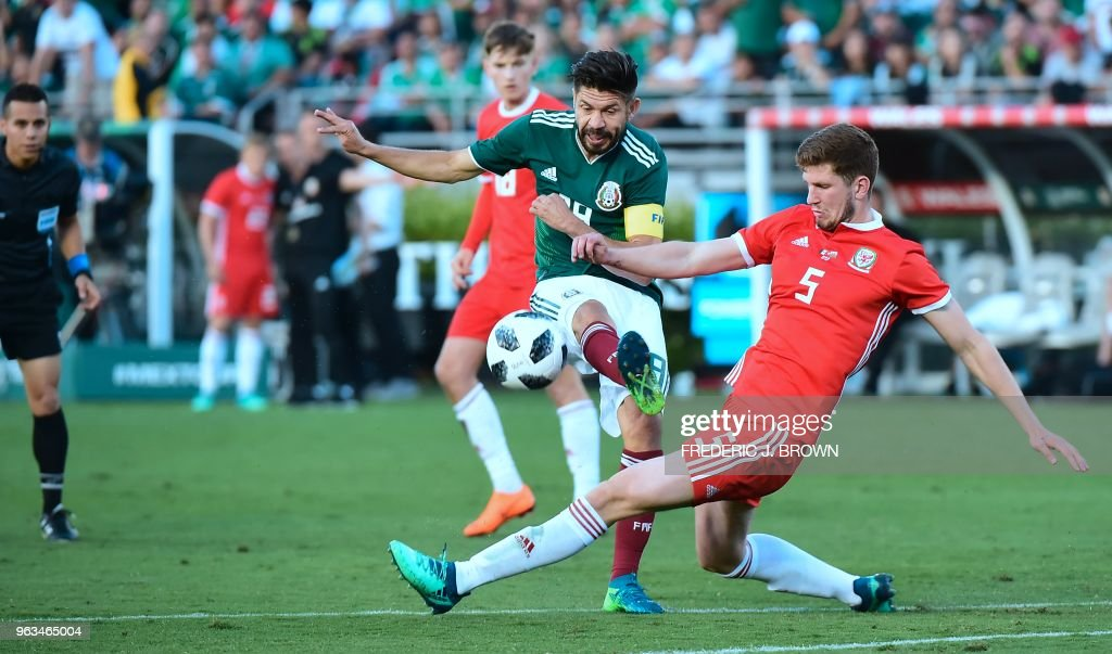 Oribe Peralta of Mexico shoots on goal while under pressure from Chris Mepham of Wales (R) during their international football friendly at the Rose Bowl in Pasadena, California on May 28, 2018 where the game ended 0-0.