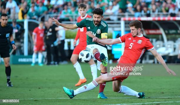 Oribe Peralta of Mexico shoots on goal while under pressure from Chris Mepham of Wales during their international football friendly at the Rose Bowl...