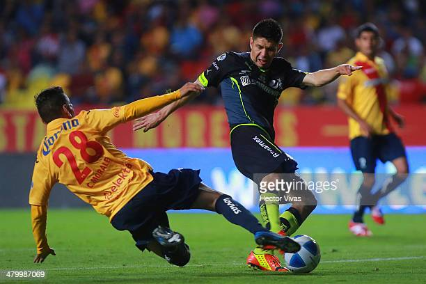 Oribe Peralta of Santos struggles for the ball with Carlos Morales of Morelia during a match between Morelia and Santos Laguna as part of the 12th...