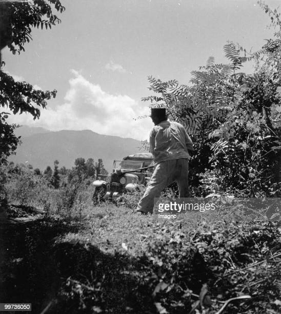 Orient Expedition of the Austrian Mr. Von Kummer: A man is standing near to a lane and is cutting the shrubs. In the background is a car of the...