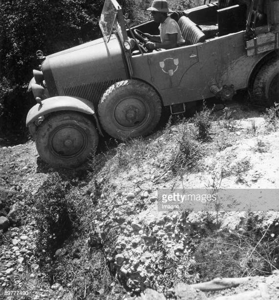 Orient Expedition of the Austrian Mr. Von Kummer: a man try's to drive the car through a rough road. Photograph. Around 1930.