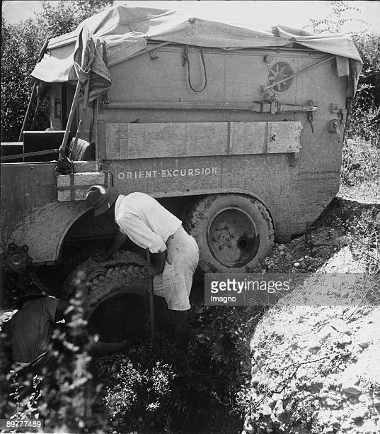 Orient Expedition of the Austrian Mr. Von Kummer: Two men are trying to get the stucked car going again. The wheels are not working anymore. One man...