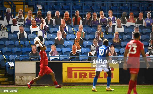 Orient player Joe Widdowson takes a throw in as cardboard cut out fans including Chewbacca from Star Wars look on from the stand during the Sky Bet...