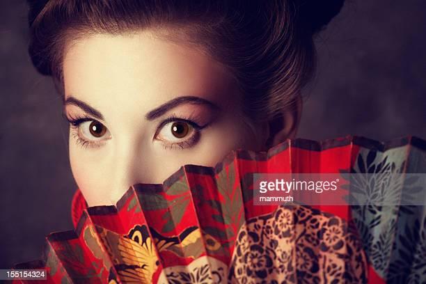 oriental beauty peeking out from behind a fan
