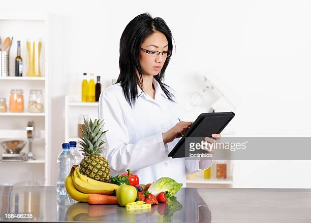 oriental healthcare professional using tablet pc - nutritionist stock pictures, royalty-free photos & images