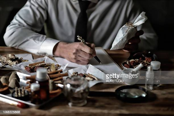 Oriental medical doctor checking prescription medicine
