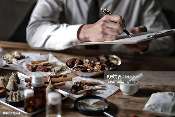 Oriental medical doctor checking various dried herbal medicine