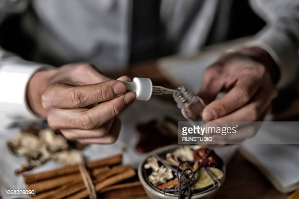 Oriental medical doctor dropping pipette