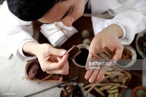Oriental medical doctor examining cinnamon