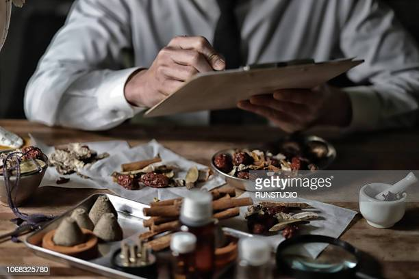 Oriental medical doctor examining various dried herbal medicine
