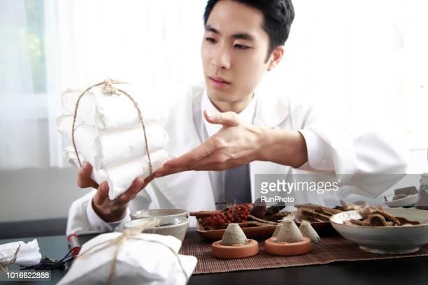 Oriental medical doctor giving prescription bag