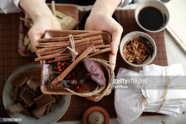 Oriental medical doctor hand holding Plate with herbal medicine