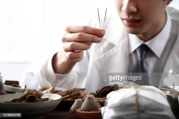 Oriental medical doctor holding acupuncture needles