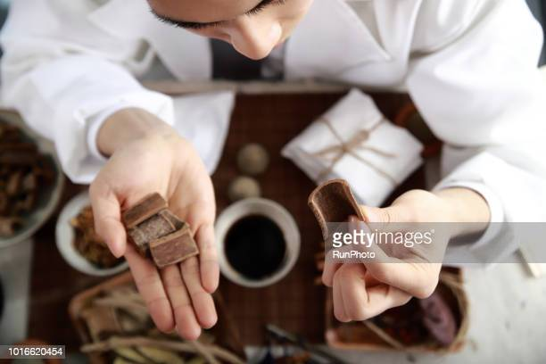 Oriental medical doctor holding cinnamon