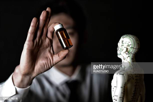 Oriental medical doctor holding liquid medicine