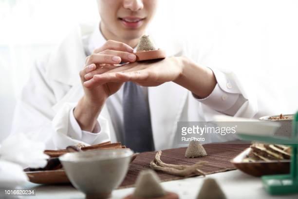 Oriental medical doctor holding moxa