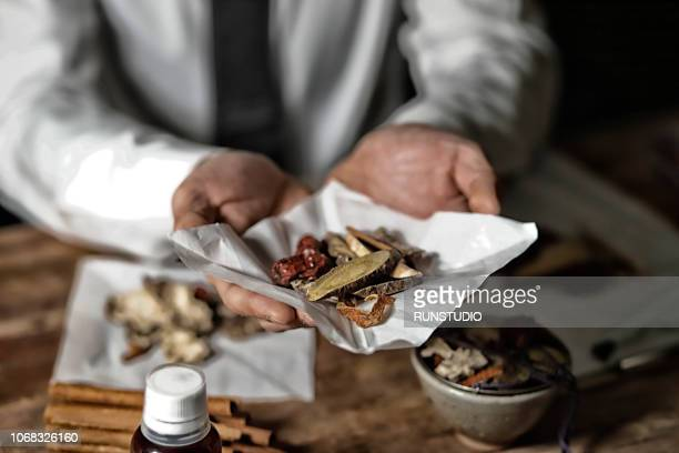 Oriental medical doctor holding various dried herbal medicine