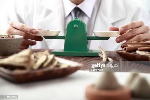Oriental medical doctor measuring herbal medicines with weighing scales