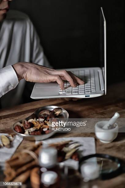 Oriental medical doctor using laptop