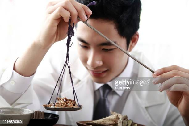 Oriental medical doctor weighing herbal medicines with scales