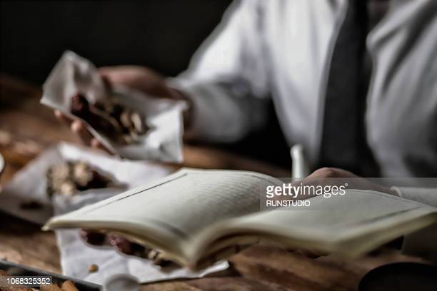 Oriental medicine doctor examining herbal medicine with book