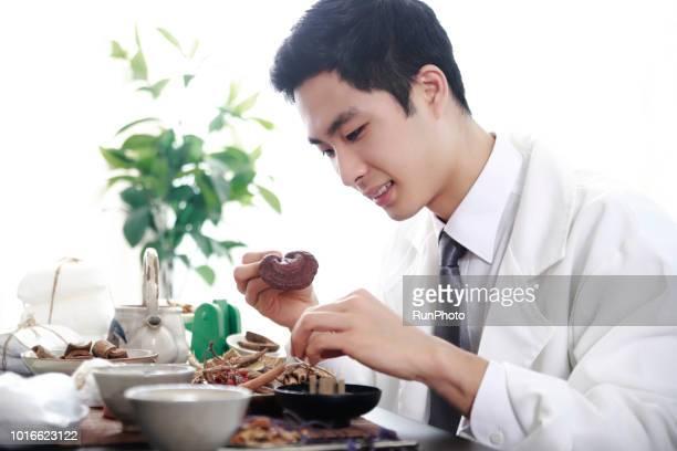 Oriental medicine doctor examining lingzhi mushroom