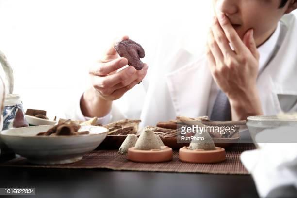 Oriental medicine doctor holding lingzhi mushroom