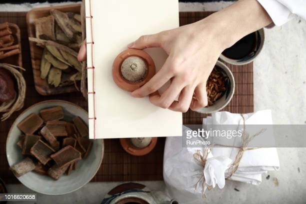 Oriental medicine doctor holding moxa cone and book