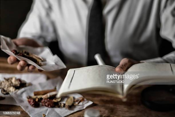 Oriental medicine doctor reading book with herbal medicine