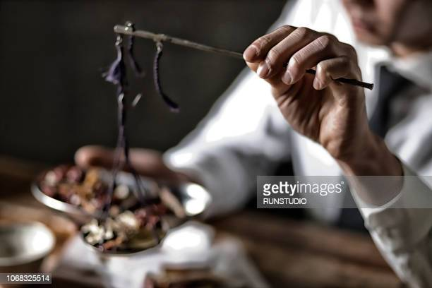 Oriental medicine doctor weighing herbal medicines with scales