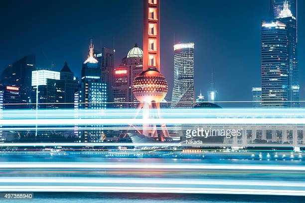 Oriental Pearl Tower with light trails from a lighted boat