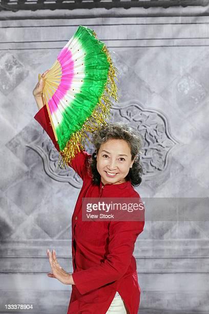 oriental senior woman dancing with fan