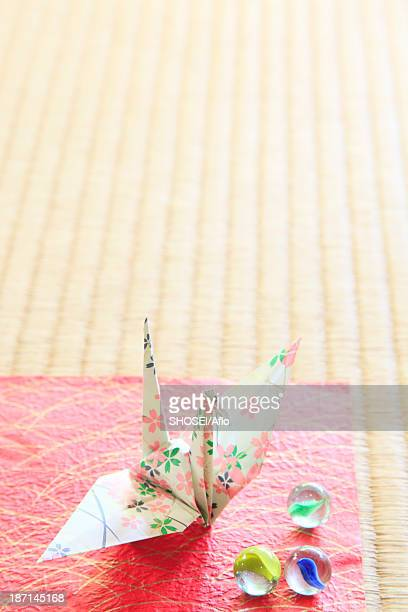 Origami crane and marbles on tatami mat