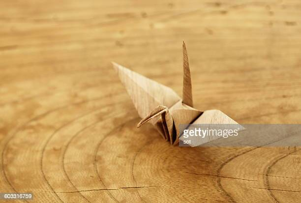 Origami crane of wood grain pattern on table
