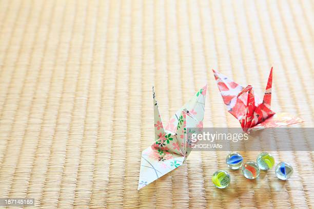 Origami cranes and marbles on tatami mat