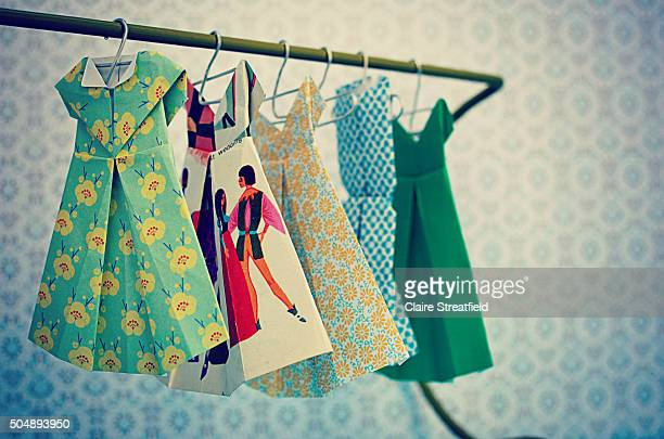 Origami fashion paper patterned dresses hanging on a wardrobe rail on metal coat hooks
