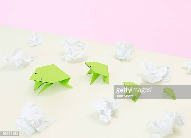 origami frogs amidst scrunched paper